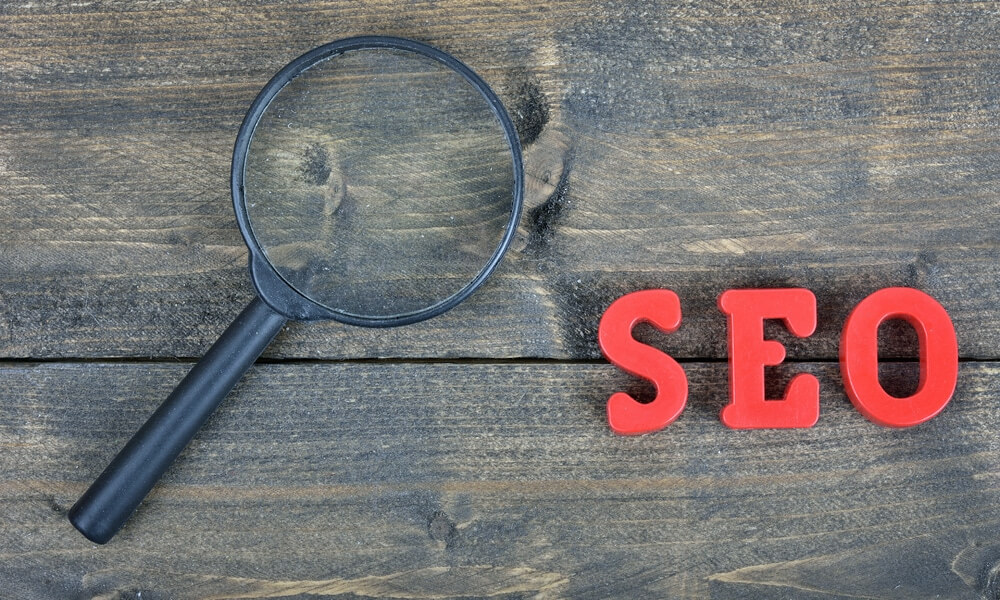 magnifying glass on a picnic table with the letters SEO